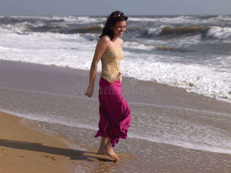 Chica joven que juega en ondas de agua fotos de archivo