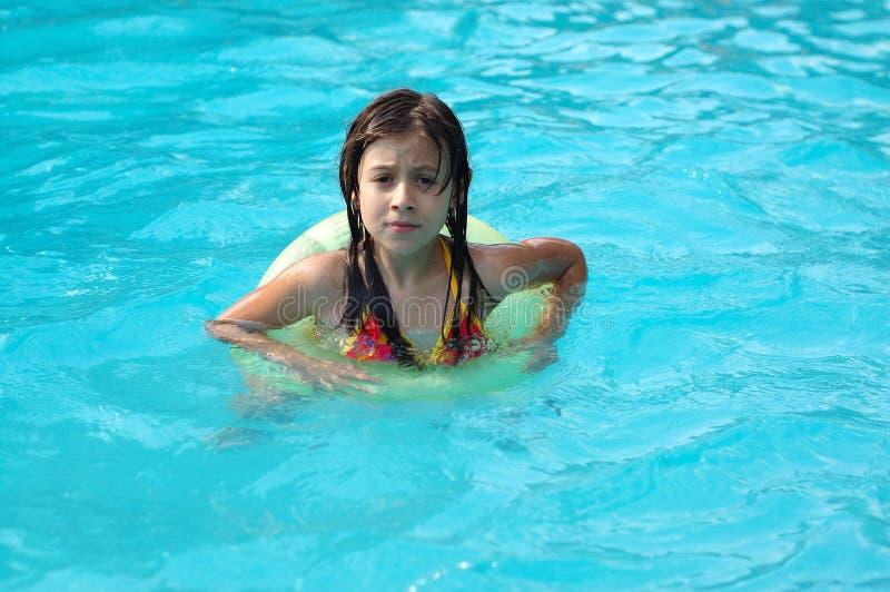 Chica joven que juega en piscina imagen de archivo