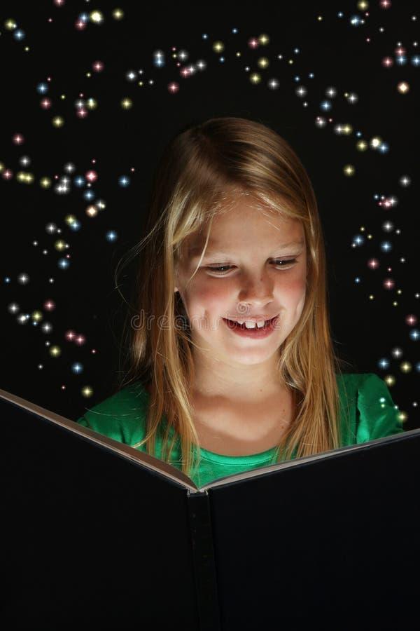 Chica joven que lee un libro de la fantasía fotos de archivo libres de regalías