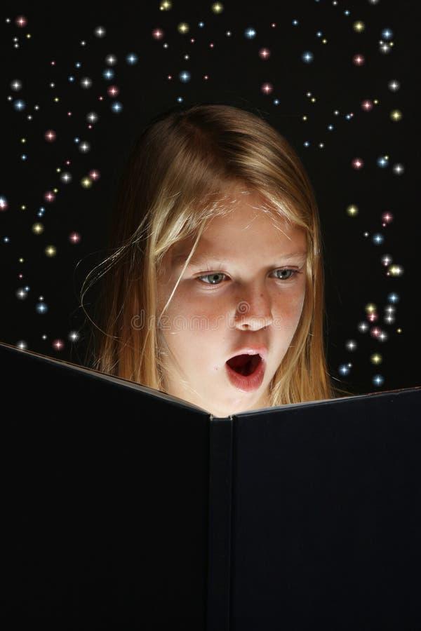 Chica joven que lee un libro de la fantasía foto de archivo libre de regalías