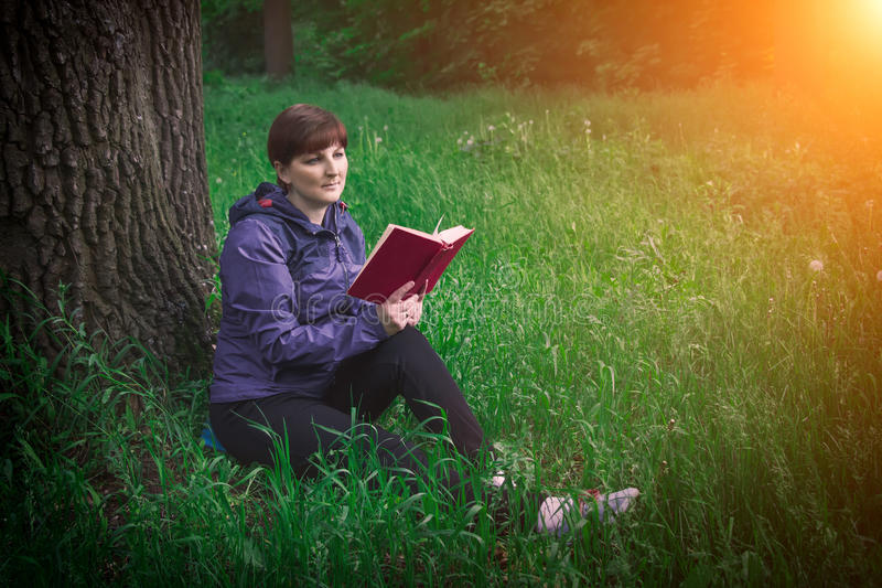 Chica joven que lee un libro que se sienta en la hierba cerca del roble en la puesta del sol Vacaciones y el acampar de verano Co foto de archivo