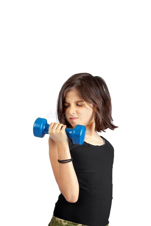 Chica joven que levanta una pequeña pesa de gimnasia de 5 libras con un Facia resuelto imagenes de archivo