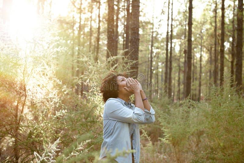 Chica joven que llama en el bosque foto de archivo