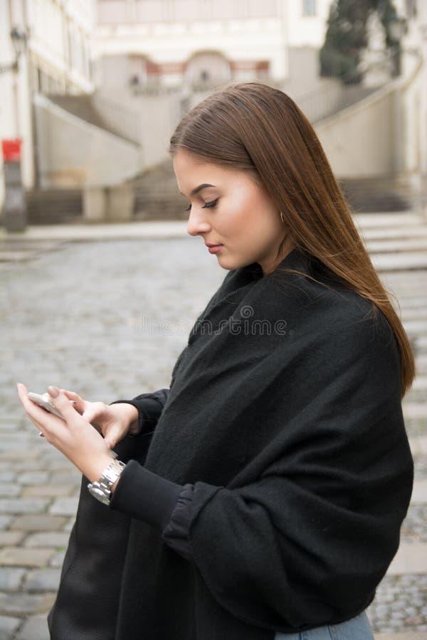Chica joven que llama por smartphone en la muchacha del streetYoung que mira al smartphone en la calle imagen de archivo libre de regalías