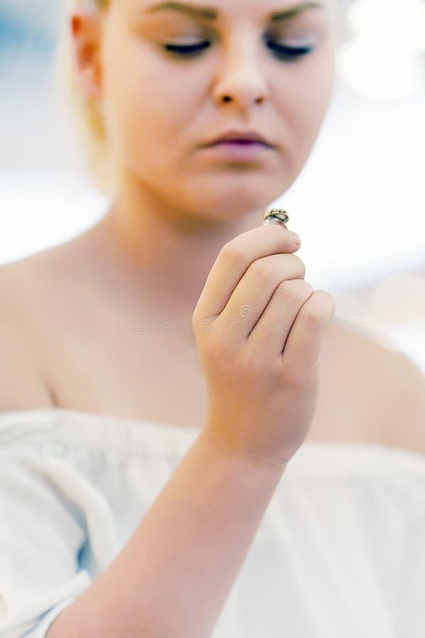 Chica joven que lleva a cabo un anillo de bodas dudoso fotografía de archivo