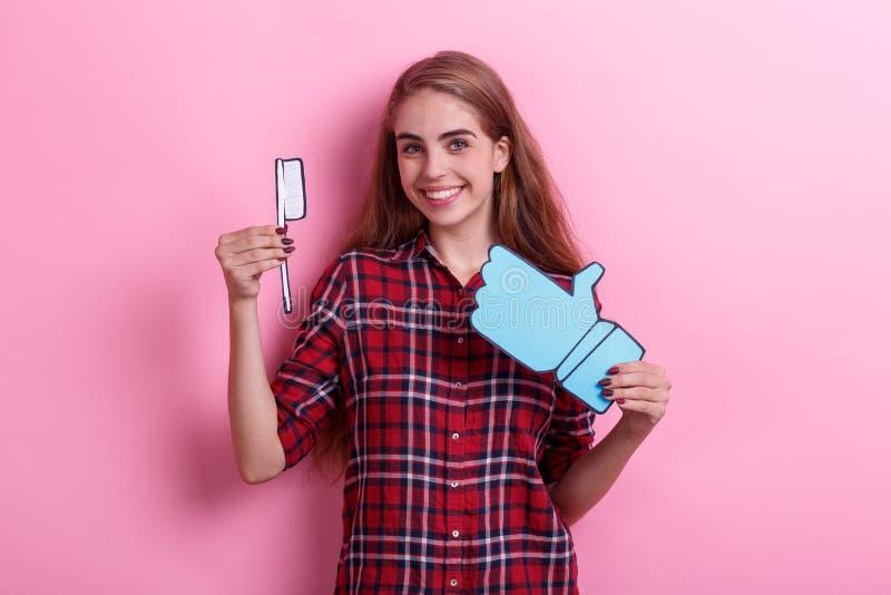 Chica joven que lleva a cabo un cepillo de dientes de papel y una muestra de la reacción y que sonríe feliz En un fondo rosado fotografía de archivo libre de regalías