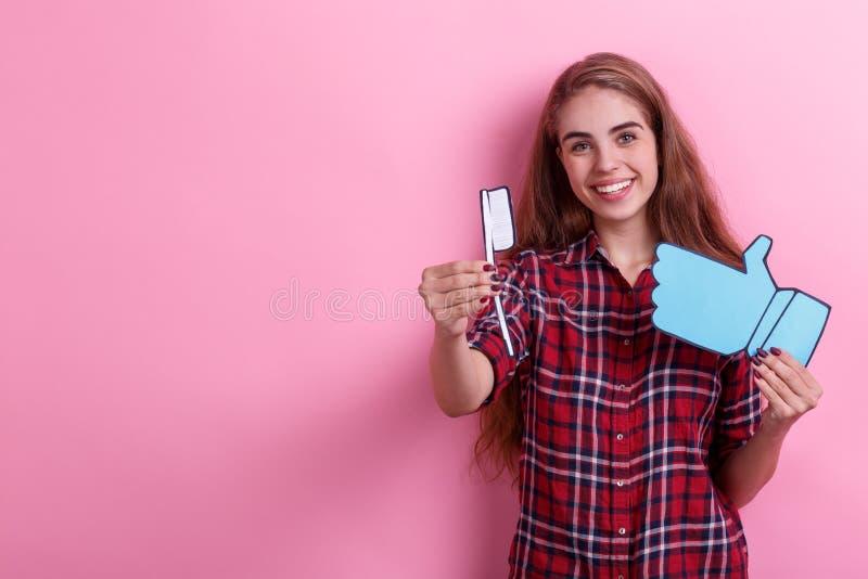 Chica joven que lleva a cabo un cepillo de dientes de papel y una muestra de la reacción y de una sonrisa Huevo en tocador imágenes de archivo libres de regalías