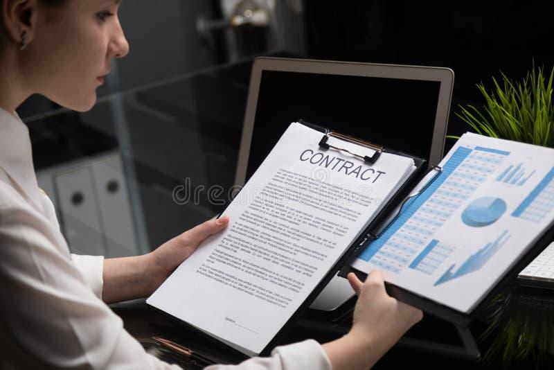Chica joven que lleva a cabo un contrato y estadísticas firmes imagen de archivo