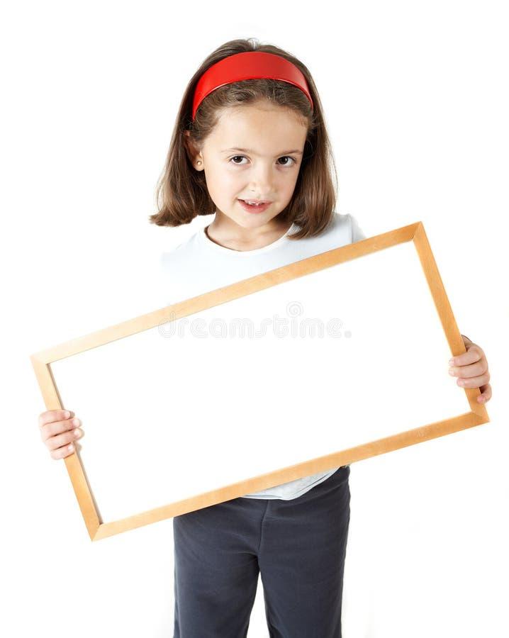 Chica joven que lleva a cabo a una tarjeta en blanco fotografía de archivo