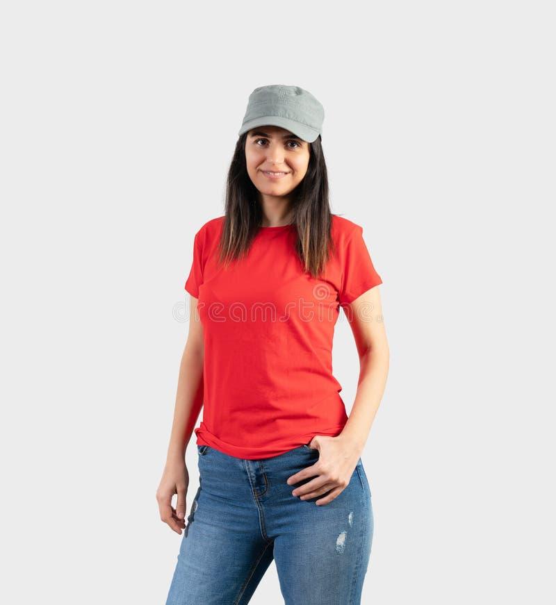 Chica joven que lleva la camiseta, el casquillo y los tejanos rojos en blanco Fondo gris de la pared fotos de archivo