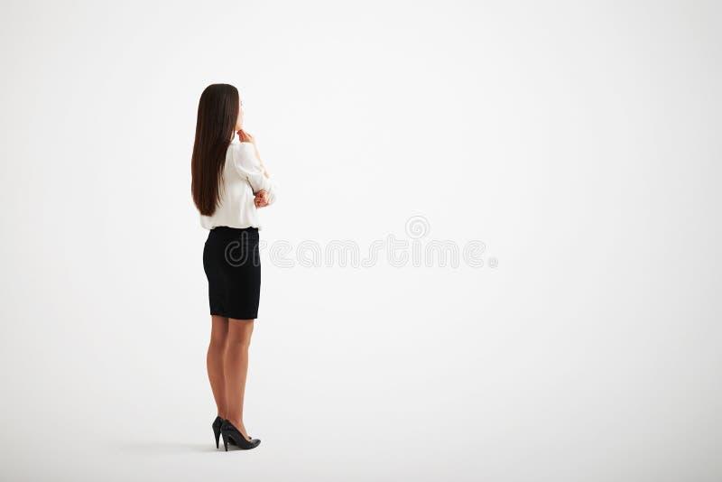 Chica joven que lleva tactos formales de la ropa a su barbilla imagen de archivo