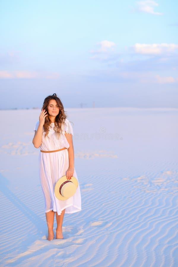 Chica joven que mantiene el sombrero, el vestido que lleva y la situación en la arena vagos fotografía de archivo libre de regalías