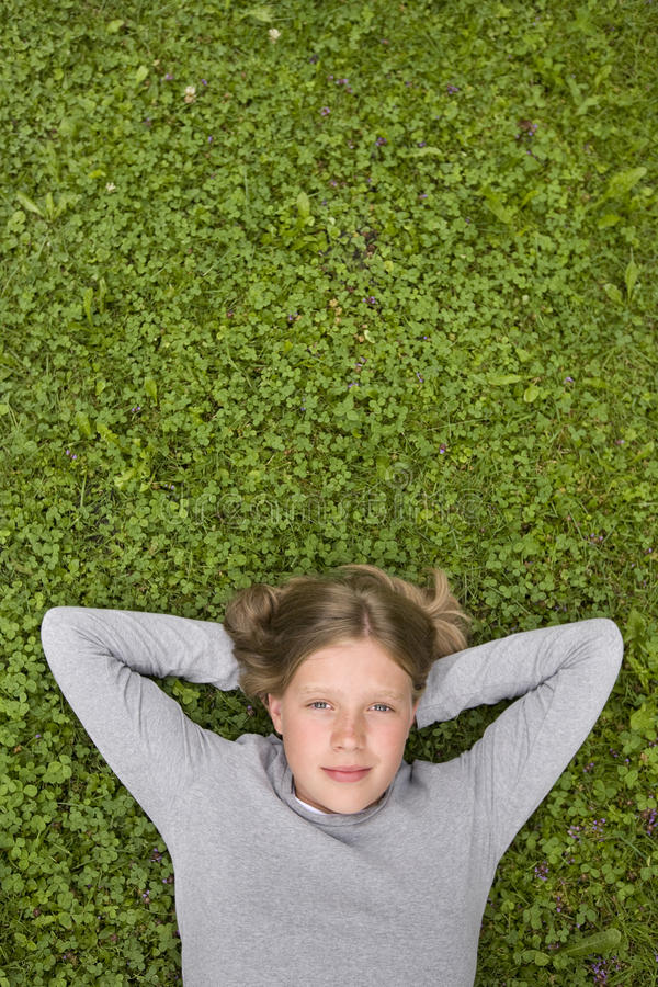 Chica joven que miente en la hierba que soña con? imagenes de archivo