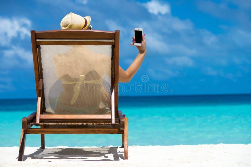 Chica joven que miente en un ocioso de la playa con el teléfono móvil a disposición foto de archivo libre de regalías