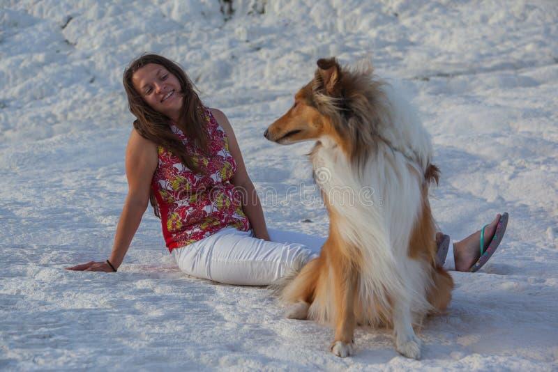 Chica joven que mira el perro del collie que se sienta en la roca blanca, Pamukkale, Turquía foto de archivo