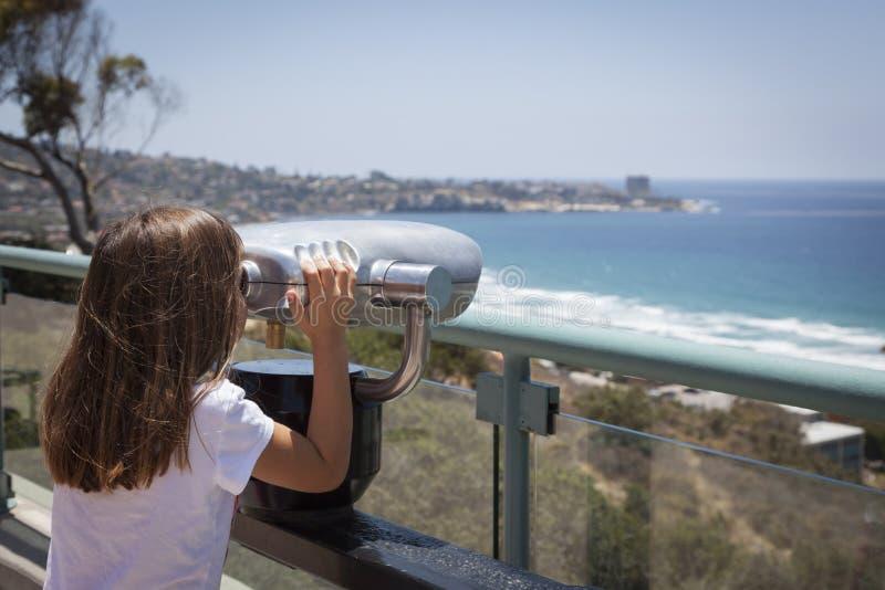 Chica joven que mira hacia fuera sobre el Océano Pacífico con el telescopio imagen de archivo libre de regalías