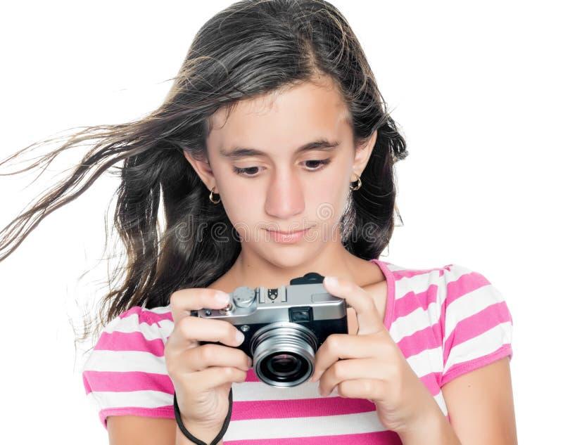 Chica joven que mira las imágenes tomadas en una cámara compacta fotos de archivo