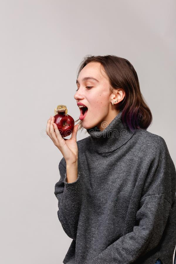 Chica joven que muerde una manzana en la cual sienta una salamandra aislamiento foto de archivo libre de regalías