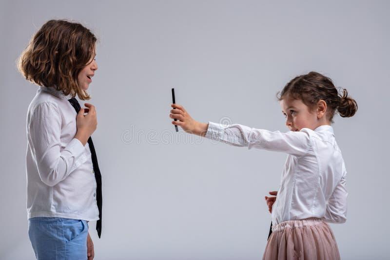 Chica joven que muestra a su hermana un teléfono móvil imagenes de archivo