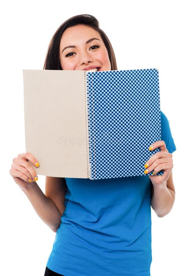 Chica joven que oculta su cara con el cuaderno imagen de archivo