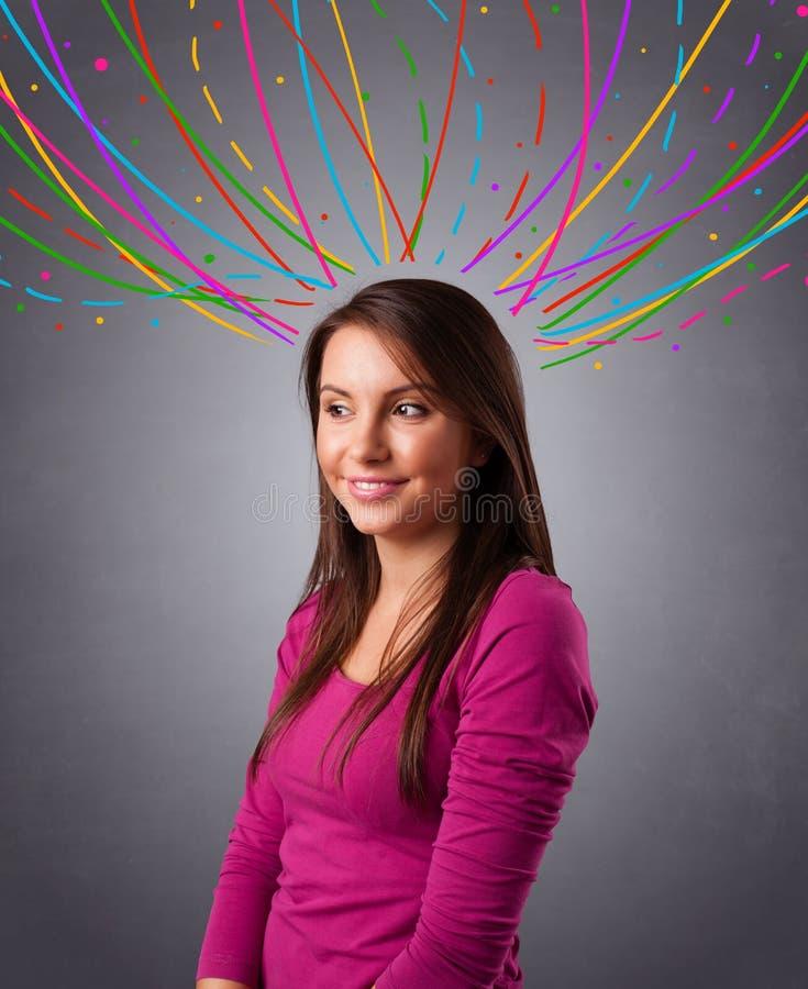 Chica joven que piensa con las líneas abstractas coloridas por encima imagenes de archivo