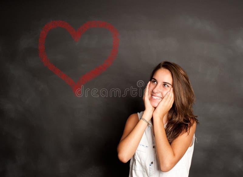 Chica joven que piensa delante de la pizarra imagenes de archivo