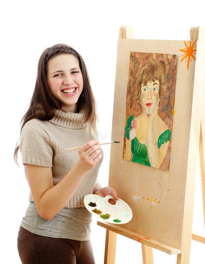 Chica joven que pinta un cuadro sobre blanco foto de archivo libre de regalías