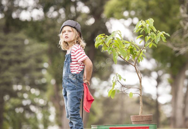 Chica joven que planta el árbol en el parque eco-enterado foto de archivo
