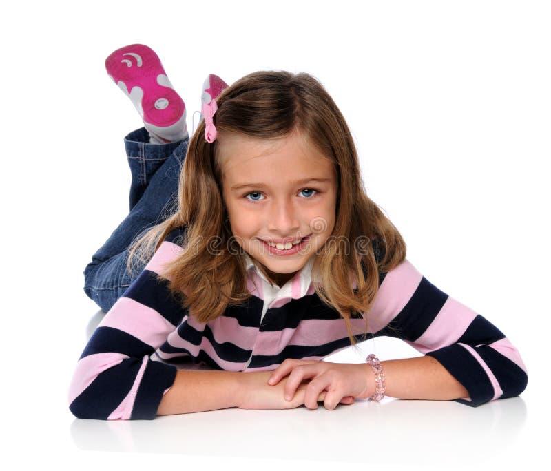 Chica joven que pone en el suelo foto de archivo