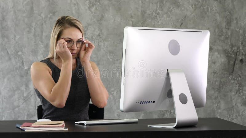 Chica joven que pone en los vidrios y comienzo que trabaja en el ordenador que se sienta en la tabla imagen de archivo