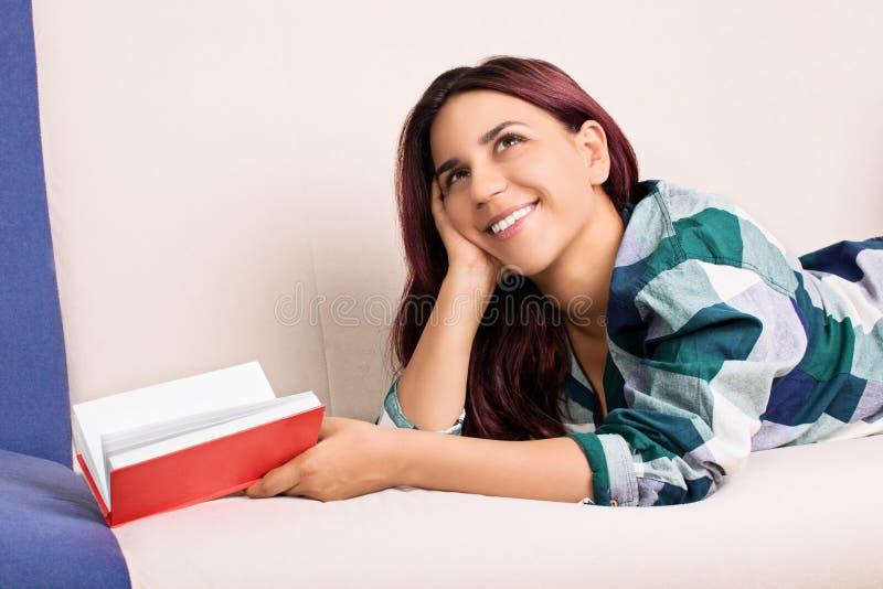 Chica joven que pone en una cama que sueña despierto mientras que lee un libro imagen de archivo libre de regalías