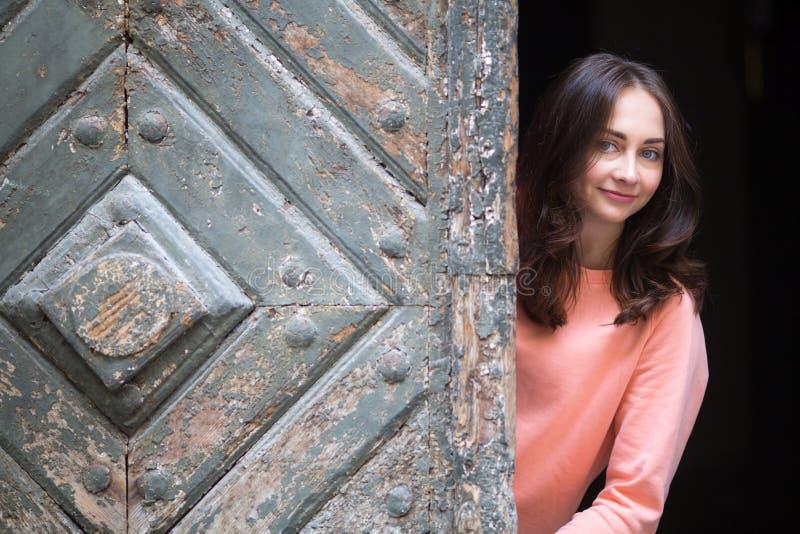 Chica joven que presenta cerca de una puerta de madera antigua imagenes de archivo