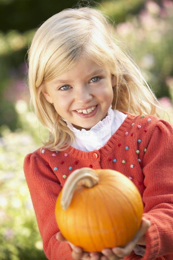 Chica joven que presenta con la calabaza en jardín foto de archivo libre de regalías