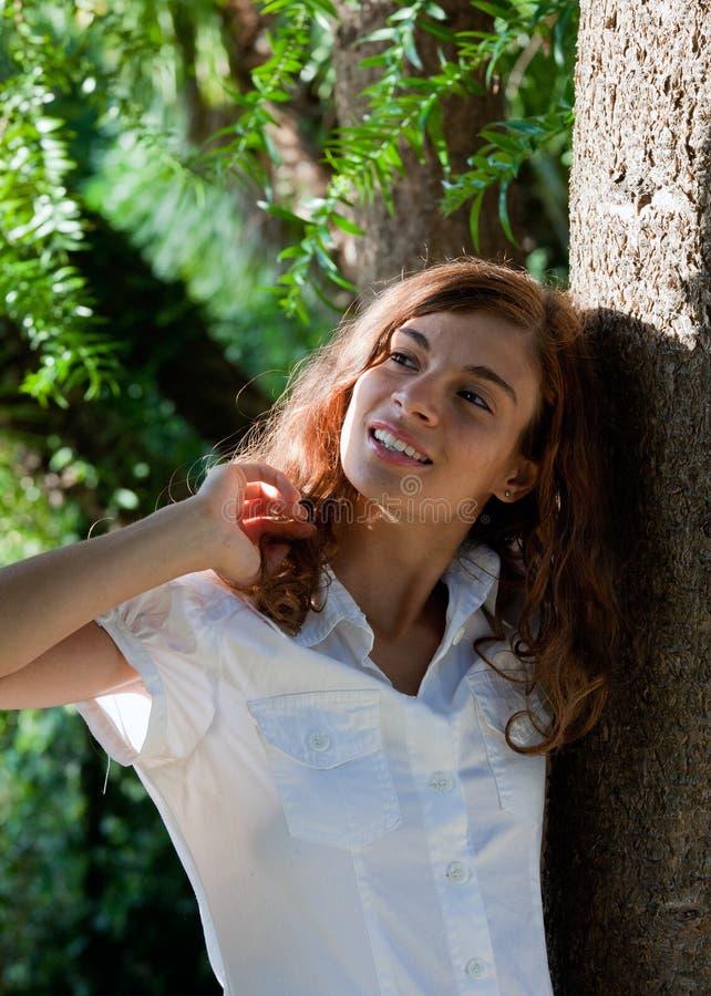 Chica joven que presenta en un jardín foto de archivo libre de regalías