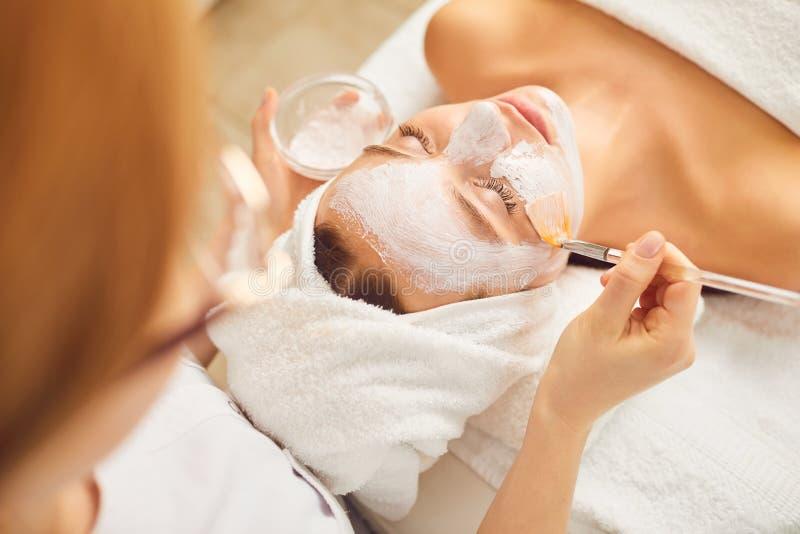Chica joven que recibe la máscara facial blanca en salón de belleza del balneario fotos de archivo