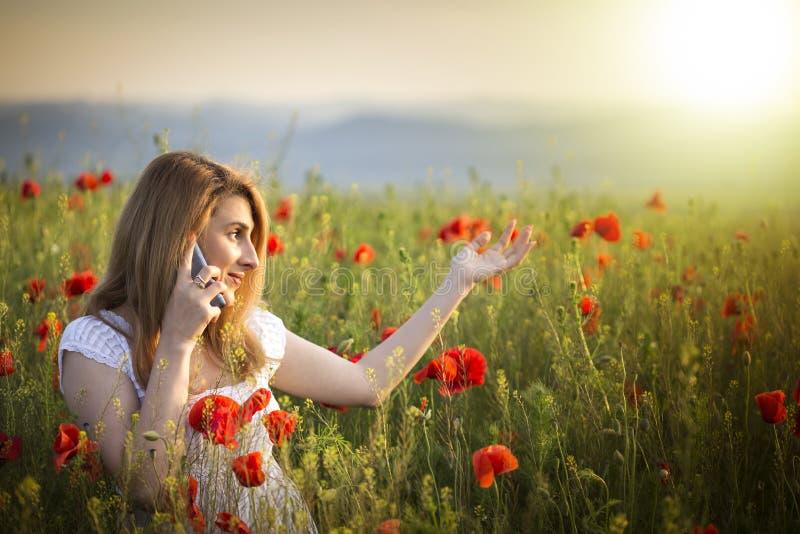 Chica joven que se coloca en un campo de la amapola que habla en el teléfono foto de archivo