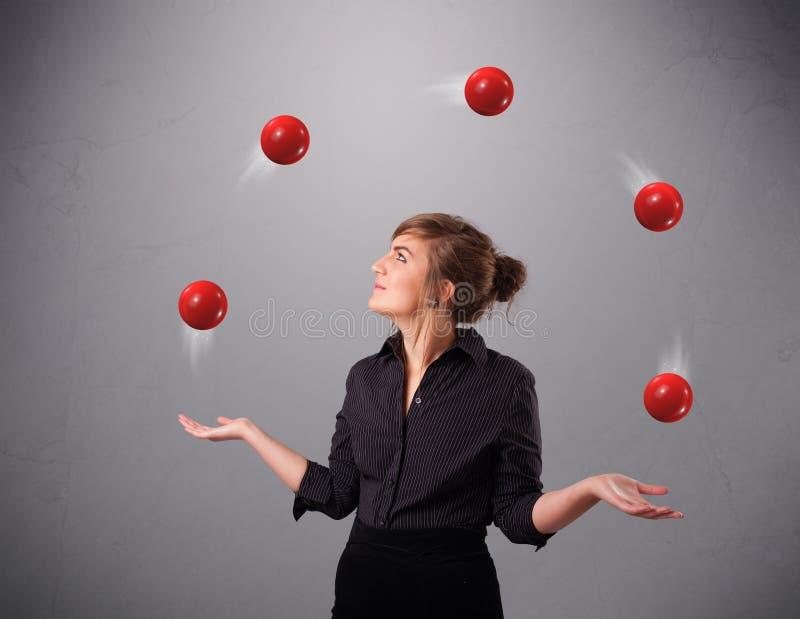 Chica joven que se coloca y que hace juegos malabares con las bolas rojas fotografía de archivo