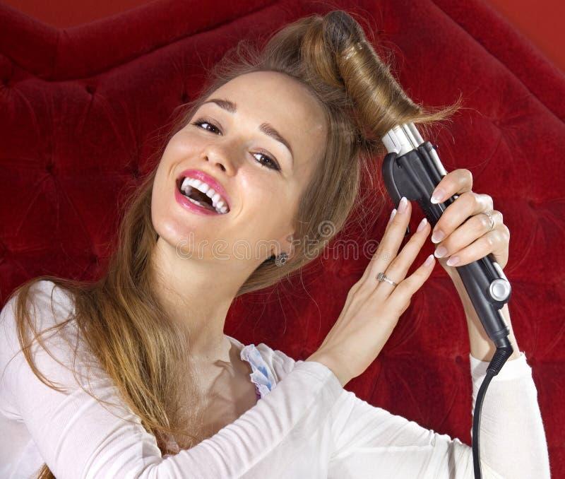 Chica joven que se encrespa el pelo foto de archivo libre de regalías