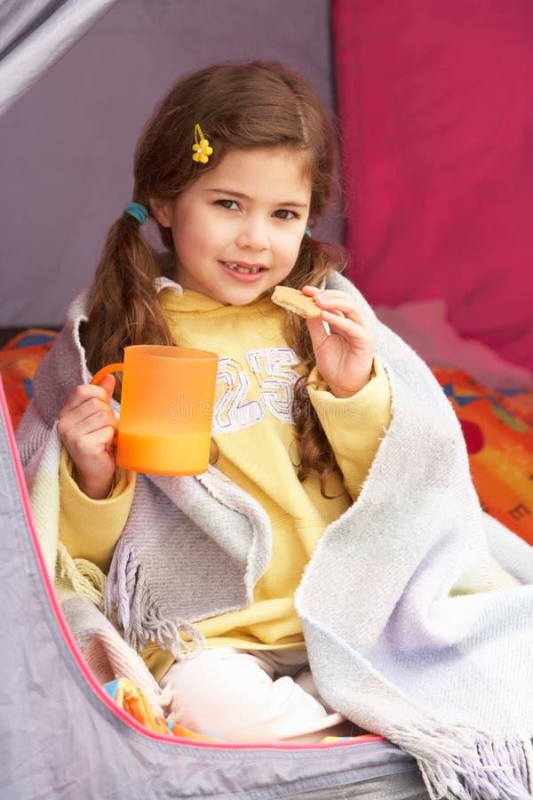 Chica joven que se relaja dentro de la tienda en acampada fotos de archivo