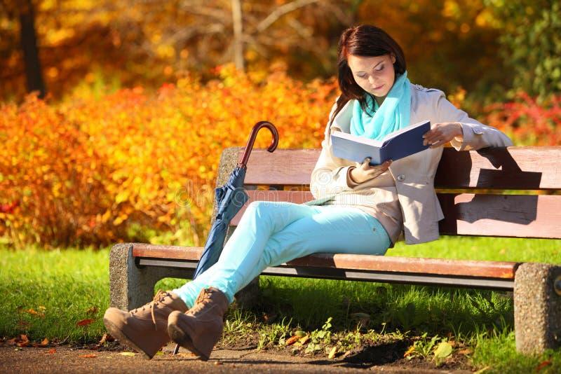Chica joven que se relaja en libro de lectura otoñal del parque fotos de archivo libres de regalías
