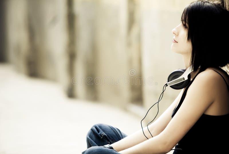 Chica joven que se sienta con los auriculares foto de archivo libre de regalías