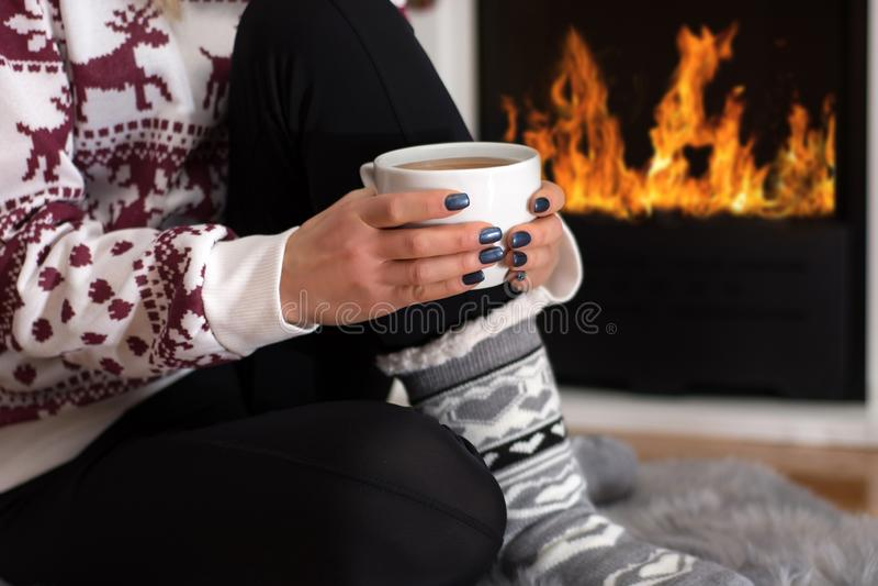 Chica joven que se sienta delante de la chimenea y que sostiene té caliente de la bebida a disposición en casa en noche larga del imagen de archivo