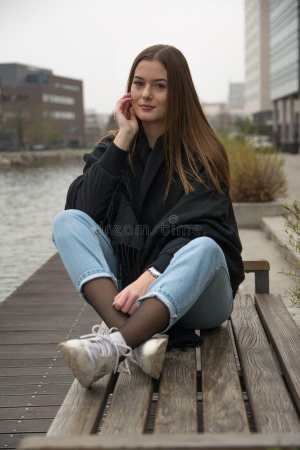 Chica joven que se sienta en el banco en ciudad imagenes de archivo