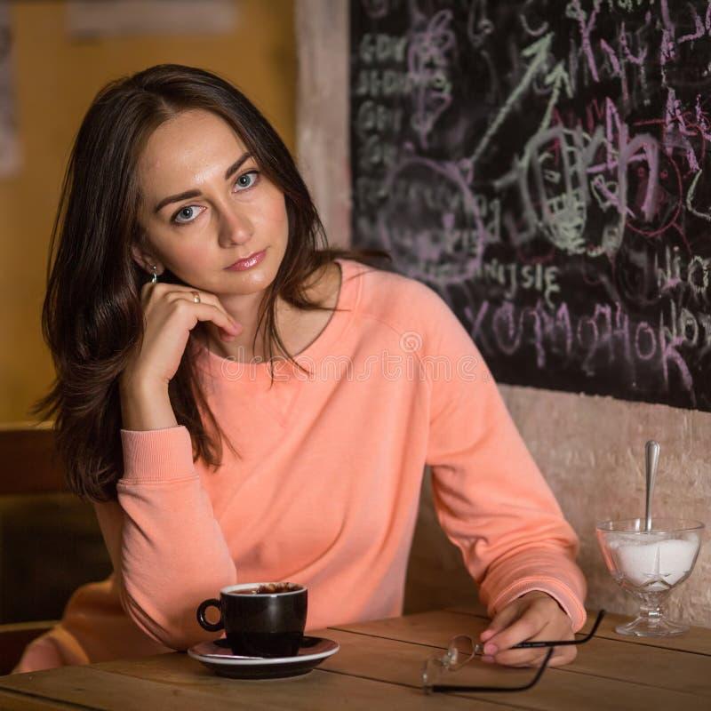 Chica joven que se sienta en el café con la taza de chocolate caliente imagen de archivo