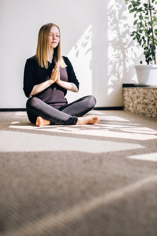Chica joven que se sienta en el piso en la actitud de la meditación imagenes de archivo