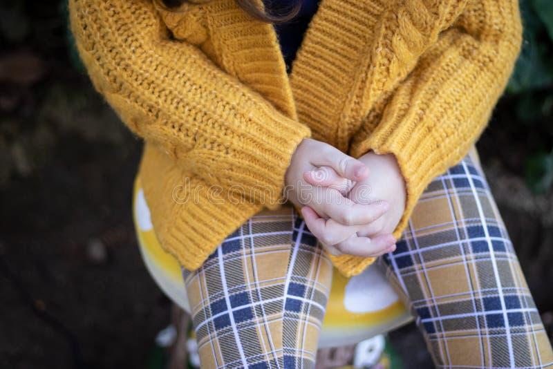 Chica joven que se sienta en el taburete que lleva a cabo las manos imágenes de archivo libres de regalías