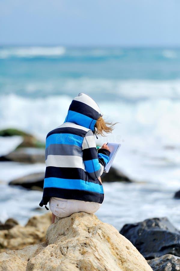 Chica joven que se sienta en la piedra imagen de archivo