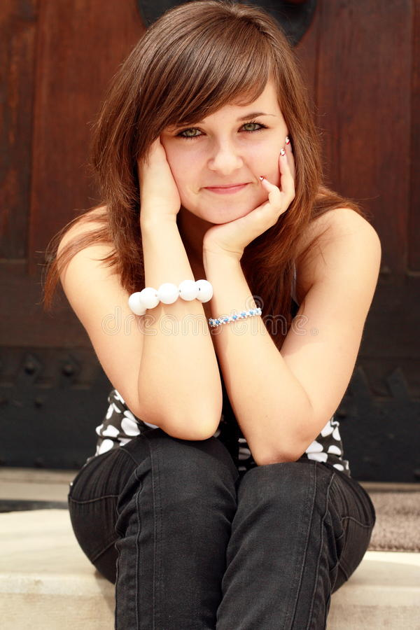 Chica joven que se sienta en las escaleras fotografía de archivo