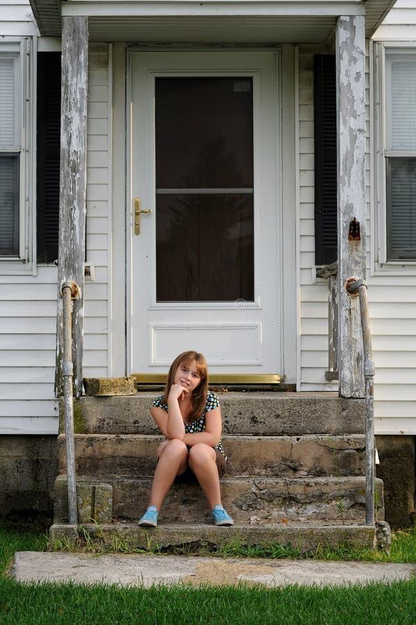 Chica joven que se sienta en pasos de progresión delanteros en casa fotos de archivo libres de regalías