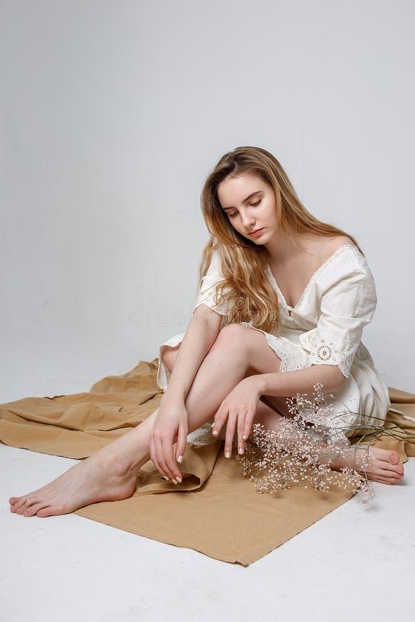Chica joven que se sienta en piso en tela beige en el fondo blanco Modelo femenino atractivo que piensa profundamente imágenes de archivo libres de regalías